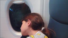 E 睡觉在飞机的年轻女孩坐由窗口 飞行生活方式在晚上 影视素材
