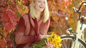 E 秋天妇女获得乐趣在公园和微笑 有长发的梦想的女孩在编织毛线衣 股票录像