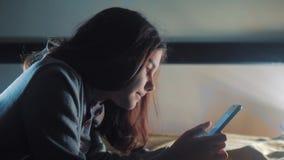 E 聊天小青少年的生活方式敞篷的女孩在社会媒介信使夜写一则消息 影视素材