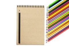E 色的铅笔,在棕色和米黄背景的笔记本 设计观念-笔记本顶视图  库存照片