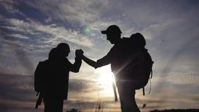 E 队游人人和妇女日落生活方式剪影帮助握手成功 股票视频