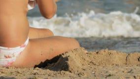 Девочка строит замок на пляже акции видеоматериалы