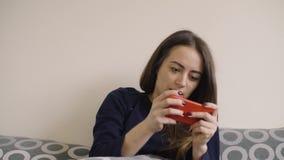 Счастливая молодая женщина играет в игру на смартфоне, лежащем дома в постели сток-видео