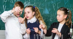 Οι σχολικοί μαθητές ομάδας μελετούν τα χημικά υγρά Σωλήνες δοκιμής με τις ζωηρόχρωμες ουσίες E στοκ φωτογραφίες