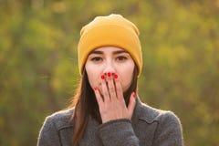 盖她的嘴的年轻女人用她的手 免版税图库摄影
