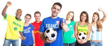Aficionado al fútbol francés con el fútbol que muestra el pulgar para arriba con otras fans Fotos de archivo