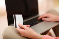 Jeune femme s'asseyant avec l'ordinateur portable et tenant le crédit Image libre de droits