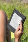 妇女室外读书的e书 免版税库存图片