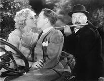 亲吻的年轻夫妇富感情地,当一个人演奏长笛时(所有人被描述不是更长生存和没有e 免版税图库摄影