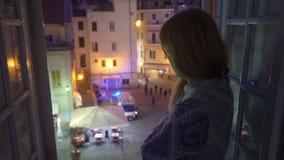 E Ambulansbil på gatan Den upphetsade unga kvinnan ser ut fönstret av hennes hus lager videofilmer