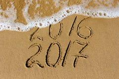 2016 e 2017 anni scritti sul mare della spiaggia Fotografia Stock Libera da Diritti