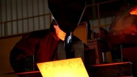 E Arbetaren kopplas in i produktion av gjutjärn Arbetaren rör långsamt vätskegjutjärn metallurgy arkivfilmer