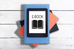 E-avläsare på bunt av böcker mot den vita lantliga trätabellen royaltyfri fotografi