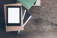 E-avläsare på bunt av böcker på träskrivbordet Royaltyfria Bilder