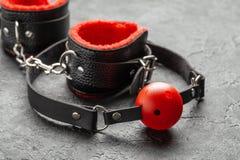 E Bâillon avec la boule rouge et menottes sur le fond noir photographie stock