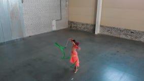 E Ballerinatanzen der jungen Frau und Ausf?hrung von den Zirkuszahlen, die einen Streifen halten stock video