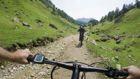 E-bici del montar a caballo del hombre del POV después de la mujer del amigo Ciclista de la acción de Mtb que explora junto la tr almacen de metraje de vídeo