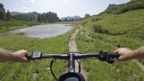 E-bici del montar a caballo del hombre del POV en la colina cerca del lago Trayectoria de exploración del rastro del ciclista de  almacen de video