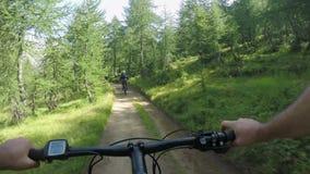 E-bicicleta da equitação do homem do POV depois da mulher do amigo Ciclista da ação de Mtb que explora junto o trajeto da fuga pe vídeos de arquivo