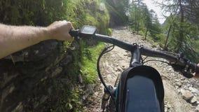 E-bicicleta da equitação do homem do POV na fuga rochosa perto do lago Trajeto de exploração do ciclista da ação de Mtb perto das vídeos de arquivo