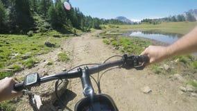 E-bicicleta da equitação do homem do POV no monte perto do lago Trajeto de exploração da fuga do ciclista da ação de Mtb perto da filme