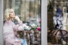 E Blondine im Rosa - blaue Töne Stadt-Café Weibliches Porträt lizenzfreie stockfotografie