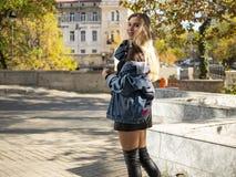 E blondynki dziewczyna z bieżącym włosy w cajg kurtki pozycji na ulicie przeciw tłu żółci drzewa fotografia royalty free