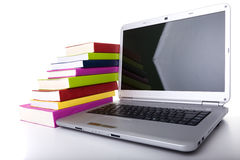 E-Book. Colorful books next to a modern laptop royalty free stock photography