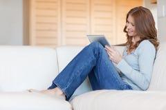 妇女在长沙发的读取e -book 免版税图库摄影