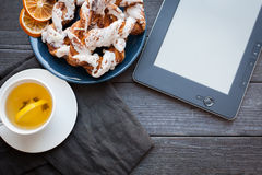 E-book and Bavarian cream puff with crushed hazelnut and lemon fudge on a blue plate. In the background a cup of green tea with le Stock Photo