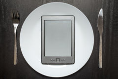 E-book lays on a white plate instead of food. Lying beside a fork and knife on a black wooden background stock photos