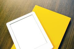 E-book and paper book on the table. Concepts of self-education royalty free stock photos
