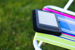 E-Book reader on the chair, green grass background Stock Photo