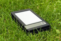 E-Book Reader in the grass. Portable electronic book lying on the grass Royalty Free Stock Photos