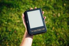 E-Book reader in hand, green grass background Stock Photos