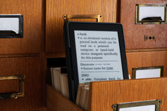 E-book Reader in Library Catalog Card Drawer - New Technology Con. E-book reader displaying dictionary page with e-book entry in a drawer of a library cards Royalty Free Stock Photos