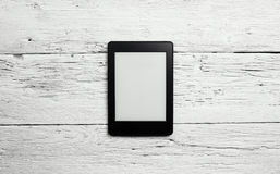 E-book reader or tablet pc on wood Royalty Free Stock Photo