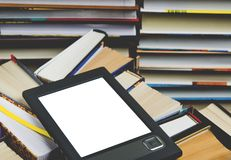 The e-book with a white screen lies on the open multi-colored books that lie on a dark background, close-up. The e-book with a white screen lies on the open stock photography