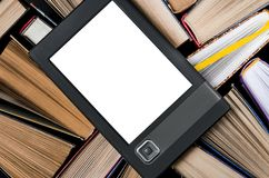 The e-book with a white screen lies on the open multi-colored books that lie on a dark background, close-up. The e-book with a white screen lies on the open royalty free stock image