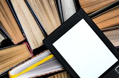 The e-book with a white screen lies on the open multi-colored books that lie on a dark background, close-up. The e-book with a white screen lies on the open royalty free stock images