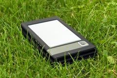 E-Buch Leser im Gras lizenzfreie stockfotos