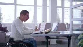 E-business of handicapped, Successful disabled man spectacled on wheelchair works on smart laptop computer during remote stock video footage