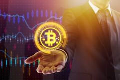 E-business and trade concept. Businessman hand holding creative digital bitcoin on abstract city background with forex chart. E-business and trade concept Stock Photo