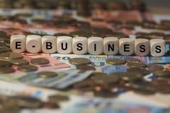 E-Business - Würfel mit Buchstaben, Geldsektorausdrücke - Zeichen mit hölzernen Würfeln Stockbild