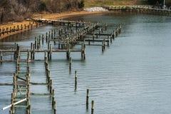 E cais velho, água azul e linha costeira arenosa no inverno Imagem de Stock