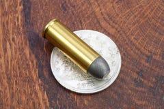 E 45 cartouches de revolver et période occidentale sauvage de dollar en argent Images libres de droits
