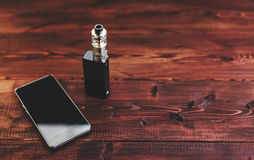 E-cig mod or electronic cigarette for vaping and smart mobile phone on a wooden. Background stock photography