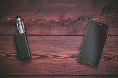 E-cig mod or electronic cigarette for vaping and smart mobile phone on a wooden. Background. Top view, close up stock photo