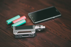 E-cig mod or electronic cigarette for vaping on a wooden table background Royalty Free Stock Photos