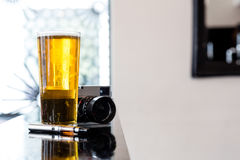 E-cigarette lying alongside beer and a camera Stock Image